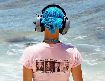 Back of woman wearing ear muffs and t-shirt. The t-shirt reads, Autism, It's Not Like You Think and Never Underestimate The Power Of The Autistic Mind.